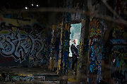 Anna Reiser sits among graffiti art in an abandoned warehouse in Blakely Harbor Park on Bainbridge Island, Washington. The park is the former site of Port Blakely Mill, which was one of the world's largest sawmills in the late 19th century.