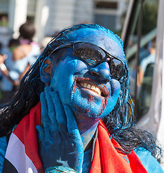 London, August 27 2017. A man smears himself with blue paint as Family Day of the Notting Hill Carnival gets underway. The Notting Hill Carnival is Europe's biggest street party held over two days of the bank holiday weekend, attracting over a million people. © Paul Davey.