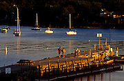 Couples walk along the Rockport pier during sunset in Rockport Maine