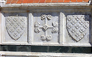 External detail from a church in Florence, Italy. Stonework reliefs, sculptures, and aesthetic embellishments adorn the outside of this church in Florence. This image shows a cross and two shields.
