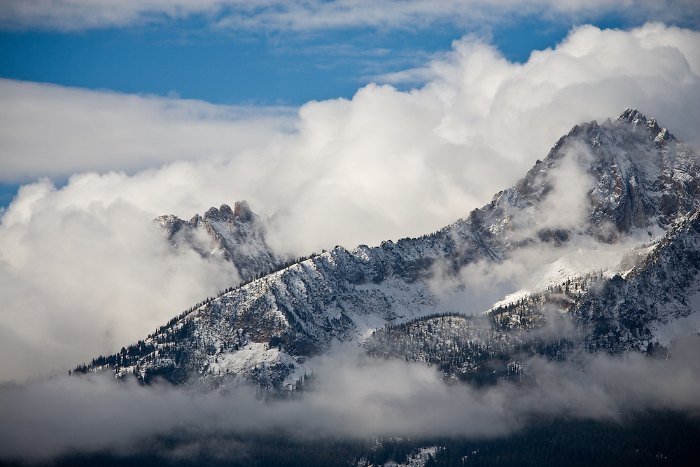 Williams Peak cloud shrouded at 10,636 feet is peaking through cloudy winter skies and early morning sub zero temperatures from Stanley in Central Idaho. Licensing and Limited Edition Prints.