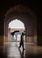 NEW DELHI, INDIA - CIRCA OCTOBER 2016: Sweeper of Jama Masjid mosque in Old Delhi. Constructed in red sandstone and white marble the mosque is a popular tourist attraction in Delhi.