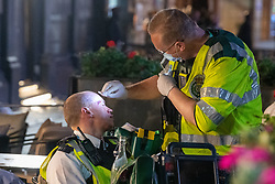 © Licensed to London News Pictures. 03/07/2021. London, UK. A police officer receives medical attention from a paramedic after he was hit in the face by a projectile thrown from the crowd, football fans had gathered in Leicester Square in central London to celebrate England's EURO2020 quarter-final football win against Ukraine, when police moved in to clear the crowd they clashed with fans and were pelted with bottles, police detained several people. Photo credit: Peter Manning/LNP
