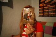 B en 2008 dans le village de Popricani. Elle montre une photo d'elle et de sa soeur jumelle quand elles étaient petites. Elle préfère rester anonyme car elle a été victime de trafic sexuel en Italie. Des mafieux moldaves lui avaient promis une place de femme de ménage dans un hôtel. Une fois arrivée en Italie, ils lui ont confisqué ses papiers et l'ont contrainte à la prostitution dans une maison close illégale. Après un raid de la police italienne, elle a été expulsée en Roumanie et protégée pendant deux ans par la police roumaine car elle a témoigné contre les mafieux. Depuis elle est repartie à l'étranger, en Suisse, où elle s'est mariée avec un Suisse. Elle a réussi à obtenir la nationalité suisse et vit en Suisse allemande aujourd'hui. <br /> <br /> B shows a picture of her and her twin sister. She prefers to remain anonymous because she was a victim of sex trafficking in Italy. She was forced to work as a prostitute in a brothel. After an Italian police raid, she was deported to Romania where she testified against the sex traffickers. After 2 years of hiding, she went back to Popricani and then left again to work illegally as a baby sitter in Switzerland. Her aim was to find a husband and acquire the Swiss citizenship, which she has managed to do. She now married and lives in Switzerland. <br /> <br />  Popricani, 2008
