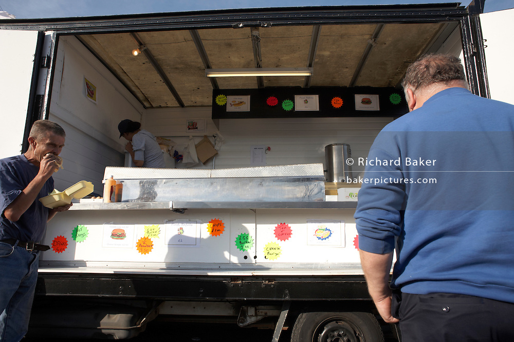 HGV drivers grab early evening fast-food dinner from a mobile burger bar trailer in an overnight lorry park on the A126 in Grays