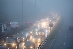 © Licensed to London News Pictures. 08/12/2020. London, UK. Traffic builds up in thick fog as commuters head into London on the A3 Kingston Bypass, South West London as the Met Office issue another yellow weather warning for freezing fog with disruption to transport for the South East of England this morning. Today a 90 year old grandmother, Margaret Keenan became the first person in the World to get an approved Pfizer Covid-19 vaccine as the government and NHS has kicked off the biggest vaccination drive in UK history. Photo credit: Alex Lentati/LNP