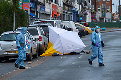 © Licensed to London News Pictures. 12/01/2021. London, UK. Forensic investigators walk past a tent on Neasden Lane North. London's Metropolitan Polcie Service were called to Neasden Lane North shortly after 21:30GMT on Monday, 11 January to reports of a disturbance. A man, believed to be in his forties, was found with stab injuries. Despite the efforts of emergency services, he died at the scene. Photo credit: Peter Manning/LNP