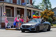 A passenger in a car waves a pride flag as they pass a by a group of demonstrators during the Mifflinburg Pride Event.
