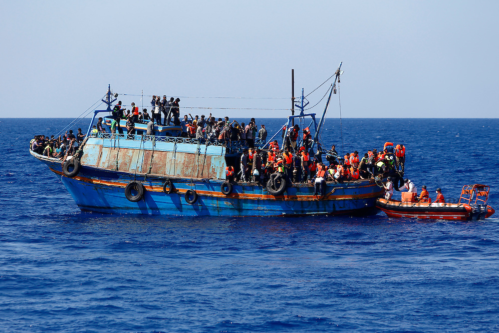 Migrants on board an overloaded wooden boat are rescued off some 10.5 miles off the coast of Libya August 6, 2015.  An estimated 600 migrants on the boat were rescued by the international non-governmental organisations Medecins san Frontiere (MSF) and the Migrant Offshore Aid Station (MOAS) without loss of life on Thursday afternoon, according to MSF and MOAS, a day after more than 200 migrants are feared to have drowned in the latest Mediterranean boat tragedy after rescuers saved over 370 people from a capsized boat thought to be carrying 600.<br /> REUTERS/Darrin Zammit Lupi <br /> MALTA OUT. NO COMMERCIAL OR EDITORIAL SALES IN MALTA