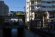 A 7000 series Tokyu Tamagawa Line train crosses a bridge above the Nomi river near Ishikawa-dai station Ota City, Tokyo, Japan. Thursday January 9th 2020