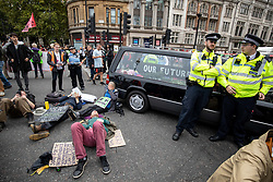 © Licensed to London News Pictures. 07/10/2019. London, UK. Climate change activists park a hearse across the road in Trafalgar Square, London, closing the road to traffic, as part of a wider two week long demonstration to cause disruption in the capital. The activists are calling for the government to acknowledge and act on climate change. Photo credit : Tom Nicholson/LNP