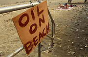 A makeshift warning sign made from plywood is roughly painted with letters declaring 'oil on beach.' It hangs on some silver railings on an unknown beach in England. The sand is strewn with sharp stones and litter and coloured (colored) a dirty brown stain high up on the shore line and more worrying, a little more distant, a father cuddles his baby child on a towel surrounded by possessions such as a cool box and the seaside toys of a happy family holiday (vacation). We look down on to this scene in disbelief that a parent lies down on such polluted terrain when health and safety considerations might have closed the entire esplanade.