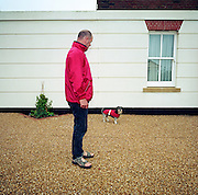On its regular morning walk and wearing a matching red coat as its owner, a small dog exercises in Holmead Road in the experimental community village of Poundbury, Dorset, England. As the mutt looks at the camera, the man waits for him to stop sniffing around before moving on. The pair stand on crunchy gravel, a deterrent for would-be thieves who might be tempted to this small town where middle-class residents live. Poundbury is the visionary model village that Charles, Prince of Wales sought to develop in 1993 as a successful and pioneering town near Dorchester, built on land owned by his own Duchy of Cornwall, challenging otherwise poor post-war trends in town planning and to some extent following the New Urbanism concept from the US except that the design influences are European..