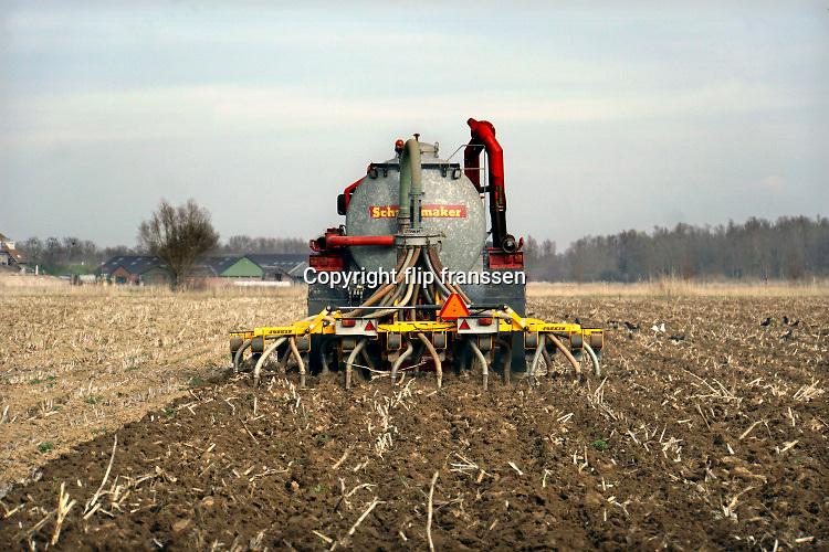 Nederland, Persingen, 21-2-2019Een loonwerker rijdt met een tractor over het land om mest in de grond, bodem te injecteren. De injecteermachine wordt steeds gevuld vanuit een gesloten laadbak waar vrachtwagens gier in pompen. Vervolgens wordt het dus naar de tractor en op het land uitgereden . Open gieren mag niet meer vanwege de hoge ammoniak uitstoot. A farmer is riding out liquid manure. The stale is injected into the soil , ground because of the environmental rules against ammonia emission. Foto: Flip Franssen