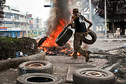 18 MAY 2010 - BANGKOK, THAILAND: An anti government protester sets up a burning tire barricade at Din Daeng Intersection in Bangkok Tuesday. The intersection has been under periodic sniper fire from unidentified snipers near Thai military lines. Violent unrest continued in Bangkok again Tuesday nearly a week after Thai troops started firing on protesters and Bangkok residents took to the streets in violent protest against the government. Tuesday was not as violent as previous days however. Although protesters continued to set up roadblocks and flaming tire barricades across parts of the city, there was not as much gunfire from the government lines. The most active protesters were at the Din Daeng Intersection about a mile from the Red Shirts' Ratchaprasong camp.  PHOTO BY JACK KURTZ
