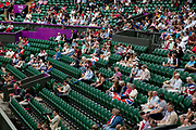 Crowds watch in Centre Court as the Tennis events at the London 2012 Olympics take place at Wimbledon. Empty seats.