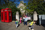 Scene or a family playing in the street by two red telephone boxes outside the Natural History Museum in South Kensington. In a selected few boroughs of West London, wealth has changed over the last couple of decades. Traditionally wealthy parts of town, have developed into new affluent playgrounds of the super rich. With influxes of foreign money in particular from the Middle-East. The UK capital is home to more multimillionaires than any other city in the world according to recent figures. Boasting a staggering 4,224 'ultra-high net worth' residents - people with a net worth of more than $30million, or £19.2million.. London, England, UK.
