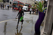Woman runs in the rain past and a pseudo-artistic plant stand feature in central London.