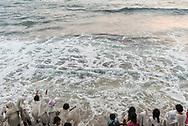 Colombo, Sri Lanka - March 29, 2017: Sri Lankan students and teachers feel the waves lap their feet at the beach at Galle Face Green in Colombo, Sri Lanka.