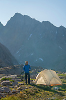 Adult male wearing blue down jacket enjoying the view at backcountry camp in Indian Basin, Harrower Peak is in the distance, Bridger Wilderness,  Wind River Range Wyoming