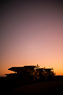 Haul trucks at sunset on the go line at a Pilbara iron ore mine site in the north west of Western Australia.