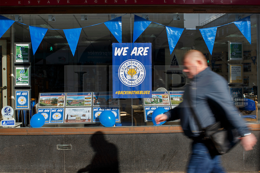 © Licensed to London News Pictures. 03/05/2016. Leicester, UK. People walk past shops with Leicester City flags as fans celebrate Leicester City winning the 2016 Premier League title the day before in Leicester city centre on Tuesday, 3 May 2016. Photo credit: Tolga Akmen/LNP