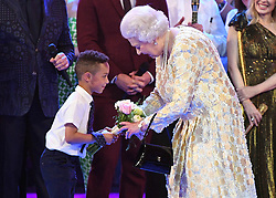 Queen Elizabeth II is presented with flowers by a young boy on stage at the Royal Albert Hall in London during a star-studded concert to celebrate her 92nd birthday.