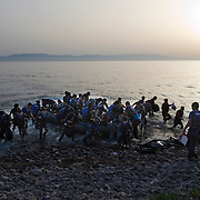 A group of Afghan refugees the moment they disembark from their small inflatable boat and land to Europe, on the beach of Skala Sykaminias. Everyday hundreds of refugees, mainly from Syria and Afghanistan, are crossing in small overcrowded inflatable boats the 6 mile channel from the Turkish coast to the island of Lesbos in Greece. Many spend their life savings, over $1000, to buy a space on those boats.