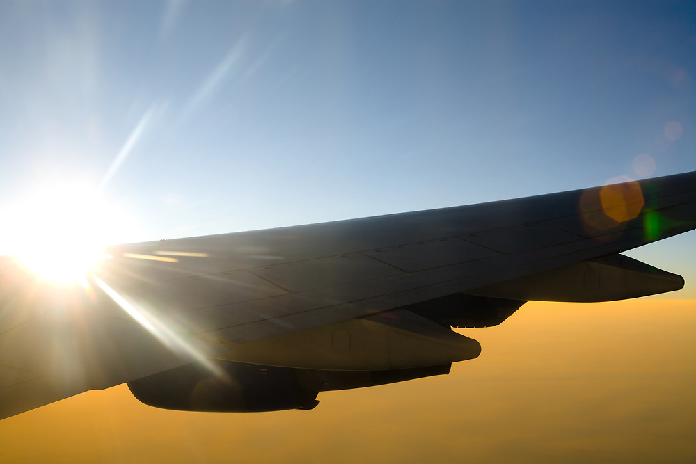 Aircraft wing against the sun with flare