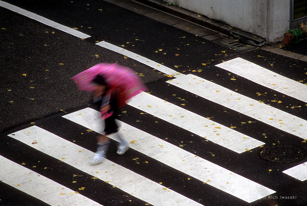 Blurred motion view of elementary school student with umbrella crossing a pedestrian crosswalk in the Asakusa district of Tokyo, Japan
