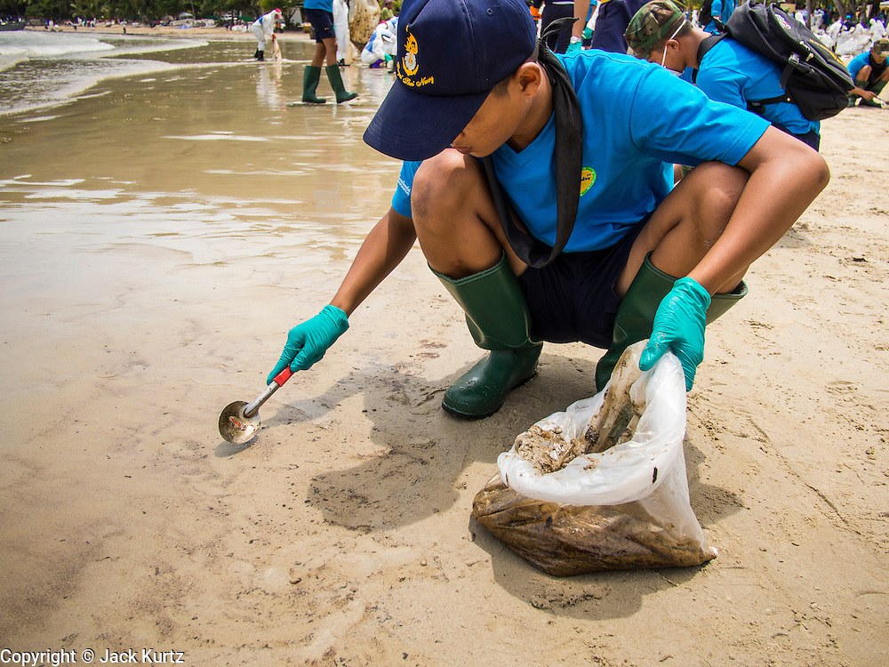 02 AUGUST 2013 - KOH SAMET, RAYONG, THAILAND: A Royal Thai Navy sailor uses a table spoon to pick up bits of sand contaminated with oil on Ao Prao beach on Koh Samet island. About 50,000 liters of crude oil poured out of a pipeline in the Gulf of Thailand over the weekend authorities said. The oil made landfall on the white sand beaches of Ao Prao, on Koh Samet, a popular tourist destination in Rayong province about 2.5 hours southeast of Bangkok. Workers from PTT Global, owner of the pipeline, up to 500 Thai military personnel and volunteers are cleaning up the beaches. Tourists staying near the spill, which fouled Ao Prao beach, were evacuated to hotels on the east side of the island, which was not impacted by the spill. Officials have not said when Ao Prao beach would reopen. PTT Global Chemical Pcl is part of state-controlled PTT Pcl, Thailand's biggest energy firm.    PHOTO BY JACK KURTZ