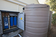 865 gallon rain barrel next to UV water filter and micron filters for harvested rainwater on a Green home that is off the grid. Solar power and a rainwater harvesting system supply all the energy and water for this home in Los Angeles, California, USA