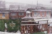 A fierce September snowstorm whips through a residential hillside area of Ulaanbaatar, Mongolia. Material World Project.