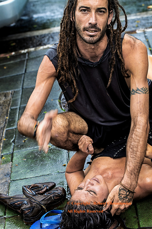Bangkok Streets: A young man in dread locks holds down a distressed, beautiful woman and awaits the police and an ambulance; claiming he was owed both his room key and money, near Khaosan Road - Bangkok Thailand.