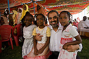 British Labour peer, Lord Ahmed of Rotherham hugs local children in a compound of the govenor of north Darfur, Osman Mohammed Yousef Kibir at Al Fashir, Sudan. Nazir, Baron Ahmed (born 1958) is a member of the House of Lords, having become the United Kingdom's first Muslim life peer in 1998 and is in this war-torn province of Sudan to attend the first-ever international Conference on Womens' Challenge in Darfur, hosted by the govenor in his own compound.