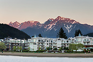 Sunset light on Mount Cheam with the waterfront condominiums at Harrison Lagoon in the foreground. Photographed from the edge of Harrison Lake in Harrison Hot Springs, British Columbia, Canada.  The mountain peaks (from R to L) are Cheam, Lady, Knight, Stewart, and Welch.