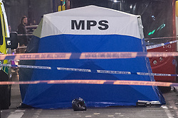 © Licensed to London News Pictures. 21/07/2021. London, UK. A motorcycle helmet sits on the ground in front of a forensic tent at the scene following a fatal stabbing on Brixton Road, Brixton. Metropolitan Police Service (MPS) were called at 20:18BST to reports of an assault close to Brixton Underground Station. Despite efforts from police officers, paramedics from London Ambulance Service (LAS) and London's Air Ambulance the man was pronounced dead at the scene at the 20:45BST. Photo credit: Peter Manning/LNP