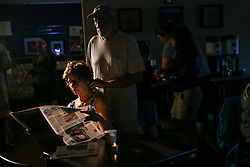 October 7, 2016 - Titusville, Florida, U.S. - STEVEN KUNTZ rubs the shoulders of his wife, CHRIS as she reads the paper in the lobby of the Hampton Inn while Hurricane Matthew rages outside. The couple from Grand Blank, Michigan came down for a short vacation at The Great Outdoors and had to evacuate from their RV. (Credit Image: © Will Vragovic/Tampa Bay Times via ZUMA Wire)