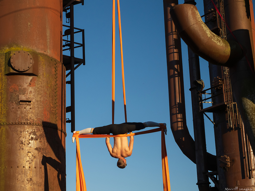 Male aerialist in industrial setting.