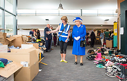 Queen Elizabeth II is shown donations of aid made by members of the local community by Executive Director of Kensington and Chelsea Council Sue Harris during a visit to the Westway Sports Centre, London, which is providing temporary shelter for those who have been made homeless in the Grenfell Tower disaster.