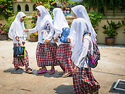 10 APRIL 2015 - BANGKOK, THAILAND: Girls walk into Masjid Ton Son in Bangkok before Friday prayers. (Masjid is the Thai word for Mosque.) A Pew Research Center study recently released identified Islam as the fastest growing religion in the world. Masjid Ton Son was the first mosque in Bangkok, founded in 1688 during the reign of King Narai, of the Ayutthaya era. Muslims are about 5 percent of Thailand, but make up a bigger proportion of Bangkok. Thailand's deep south provinces are Muslim majority.    PHOTO BY JACK KURTZ