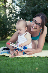 Mother and baby boy holding a picture book and laughing in lawn, Munich, Bavaria, Germany