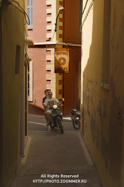 People ride bike on narrow street of Rethymno under bakery sign, Crete