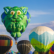 A colorful gargoyle balloon launches above others into the blue skies of Albuquerque during the city's annual Balloon Fiesta.