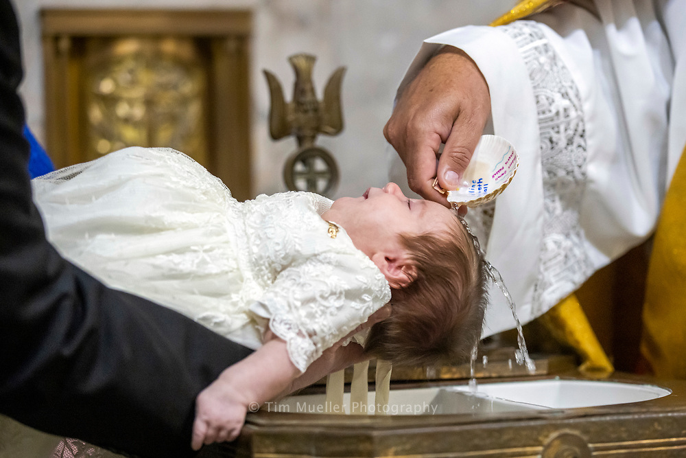 Deacon David Dawson baptizes Caroline Overall at Sacred Heart of Jesus Catholic Church.
