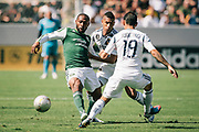 Portland Timbers midfielder Franck Songo'o, left, pass the ball away from Los Angeles Galaxy defender Sean Franklin, middle, and Galaxy midfielder Juninho during the first half of an MLS soccer match, Sunday, June 17, 2012, in Carson, Calif. (AP Photo/Bret Hartman)