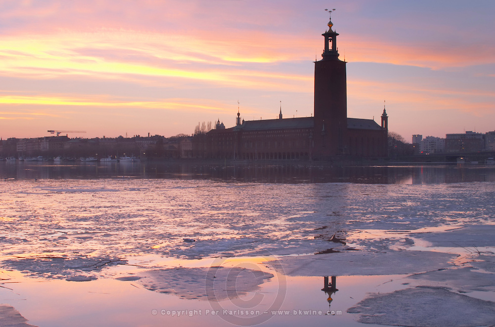 Evening view at sunset over an ice covered Riddarfjarden water towards the west with Kungsholmen and Stadshuset the Town Hall reflected in the water. Iceflakes ice flakes Stockholm, Sweden, Sverige, Europe