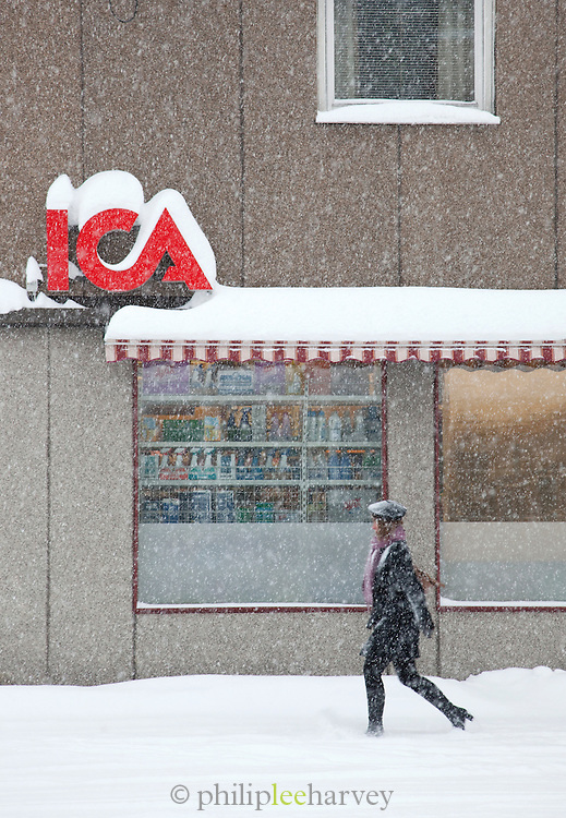 A woman walks past a local supermaket in the frozen streets of Kirkeness in Finnmark region, northern Norway