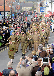 © Licensed to London News Pictures. 11/10/2014. Pickering, UK The annual wartime weekend in Pickering, North Yorkshire. People dress in 1940s period themed outfits and attend parades through the small Yorkshire town which has a traditional steam railway as would have been used in the 1940s. // Pictured: Parade of people in period uniform down Pickering Market Place.. Photo credit :  HARRY ATKINSON/LNP