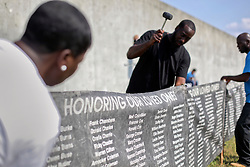 29 August 2015. Lower 9th Ward, New Orleans, Louisiana.<br /> Hurricane Katrina 10th anniversary memorial.<br /> Luther Adamson hammers the banners containing the names of hurricane Katrina victims into the ground at the point in the levee which gave way a decade ago. <br /> Photo credit©; Charlie Varley/varleypix.com.